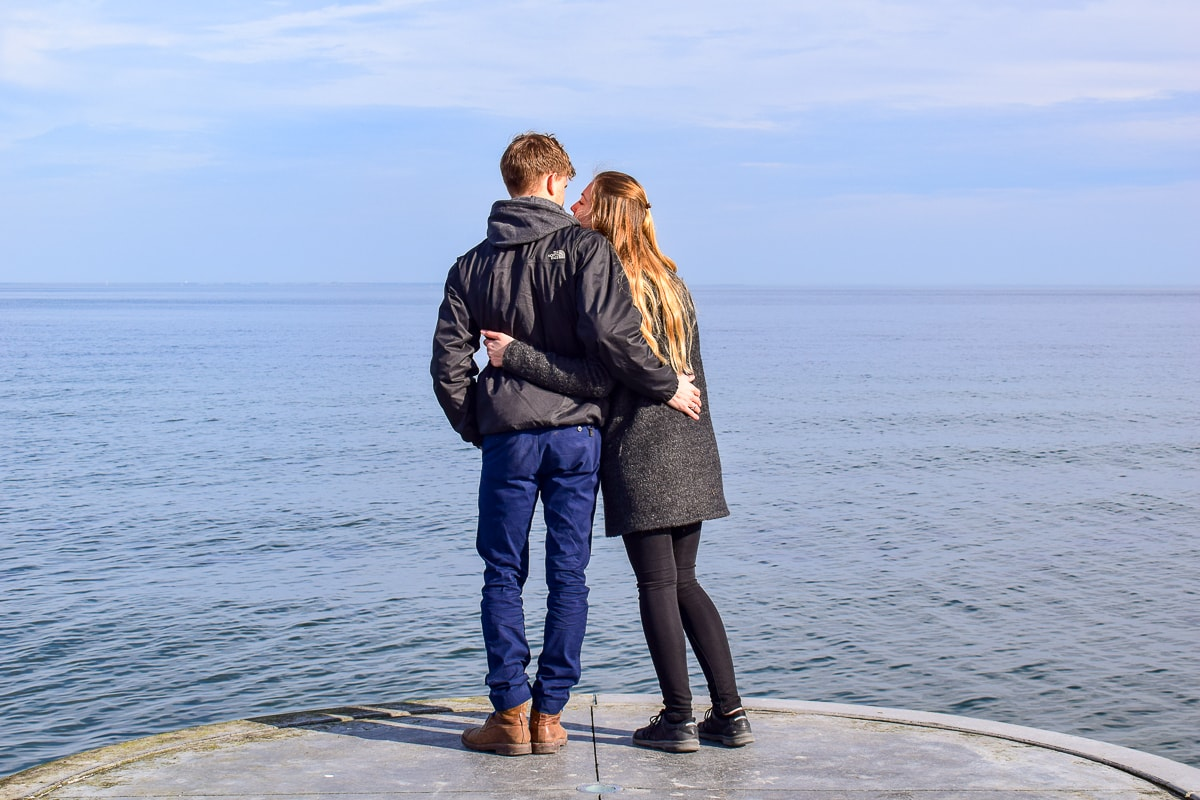 couple standing at waters edge on pier intercultural relationship