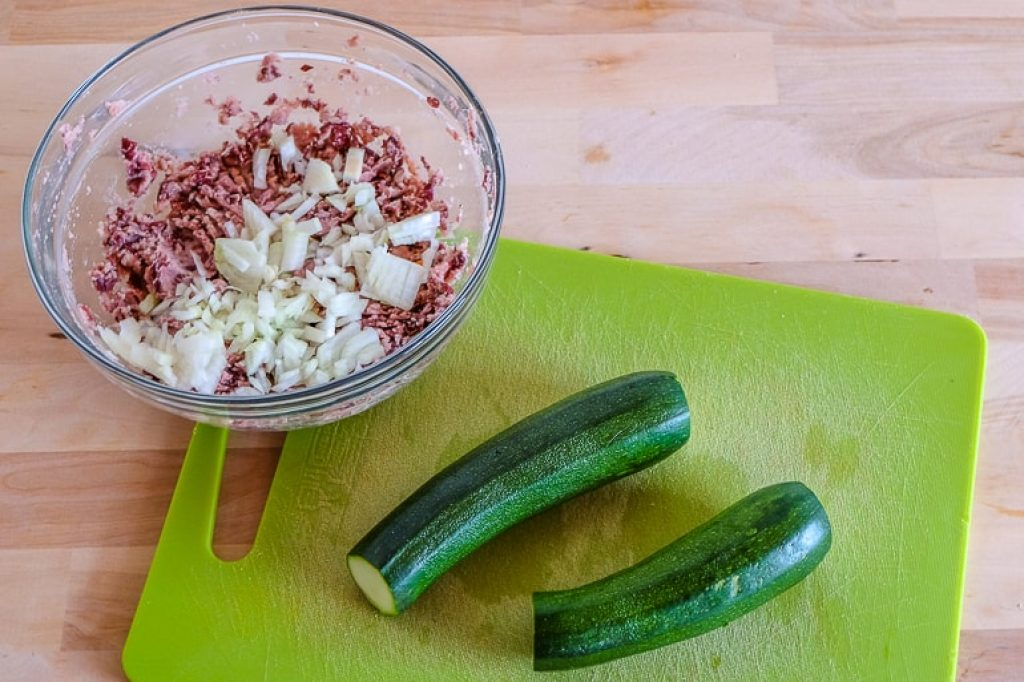 bowl with mashed food and two zucchinis on green cutting board zucchini fritters recipe