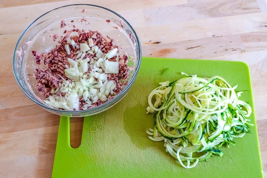 bowl with mashed food and cut up zucchini on cutting board fritters recipe