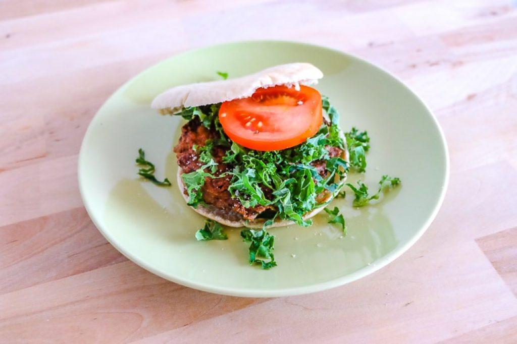 zucchini fritter in pita with tomato on green plate zucchini fritters recipe