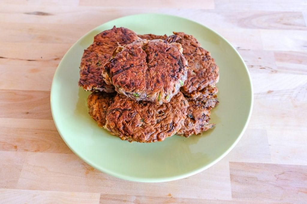 stack of fried bean zucchini fritters on green plate recipe