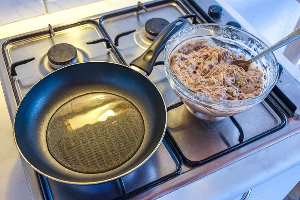 pan with oil on stove with bowl beside bean zucchini fritters recipe