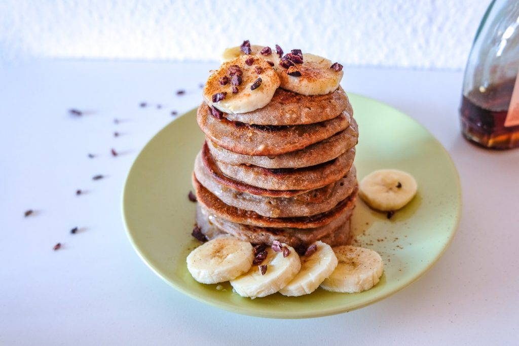 stacked pancakes on green plate with sliced bananas