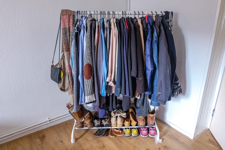 clothing rack with clothes and shoes underneath how to store your clothes without a closet or dresser