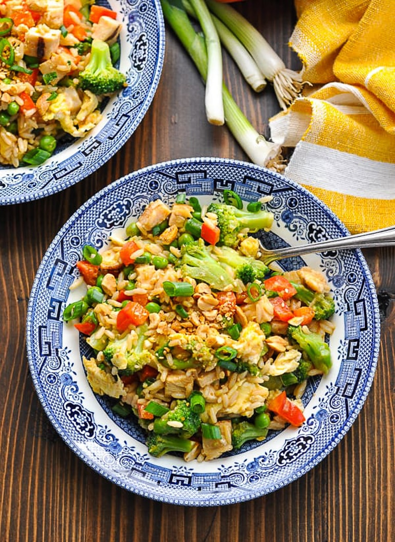 fried rice in blue bowl on table with spoon