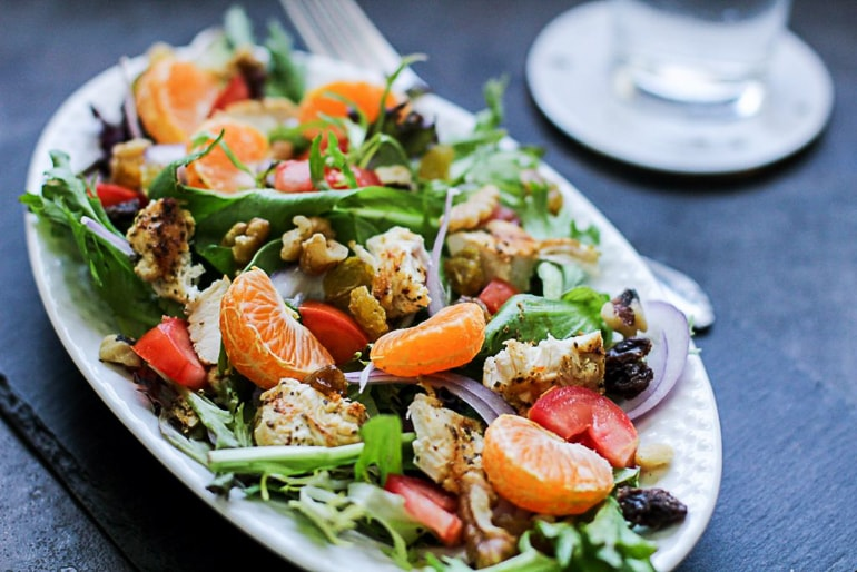 green salad with tangerine on table