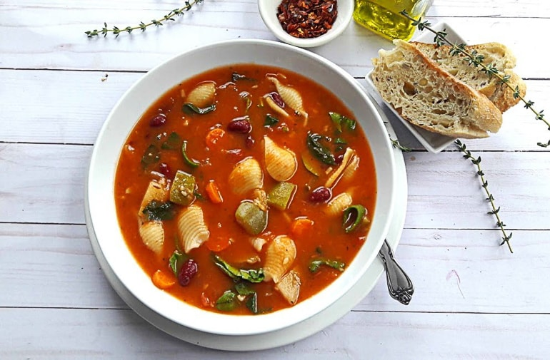 red soup with noodles in white bowl healthy minestrone soup