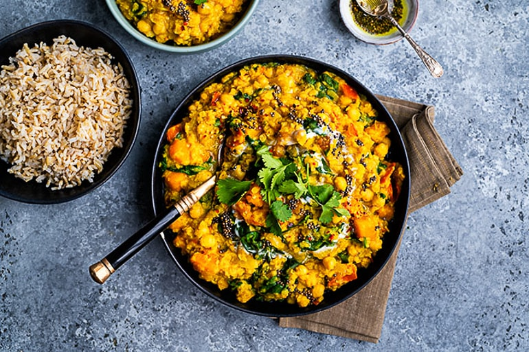 lentil and chickpea dhal in black dish in blue table