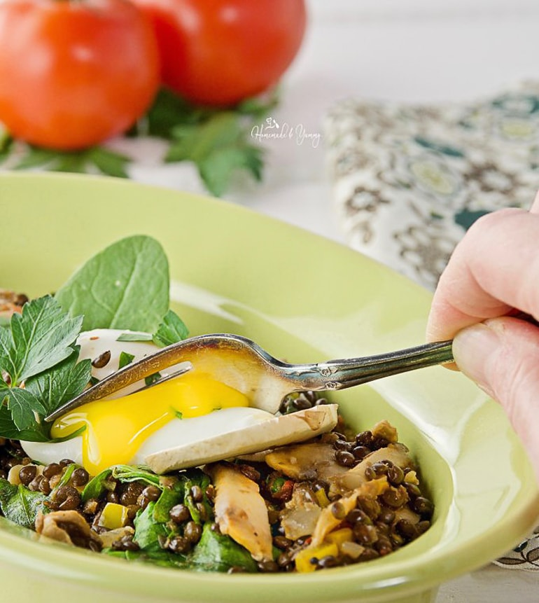 poached eggs in green bowl with lentils
