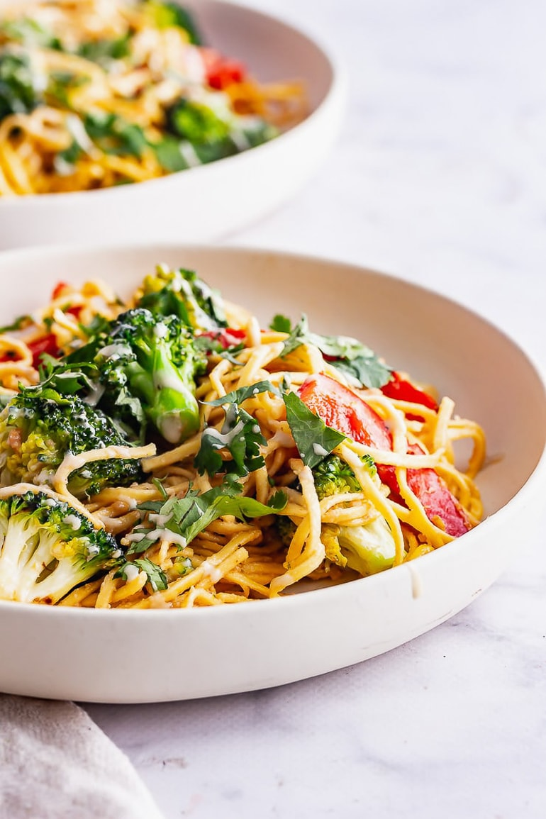 Noodle salad with broccoli and other vegetables in white bowl