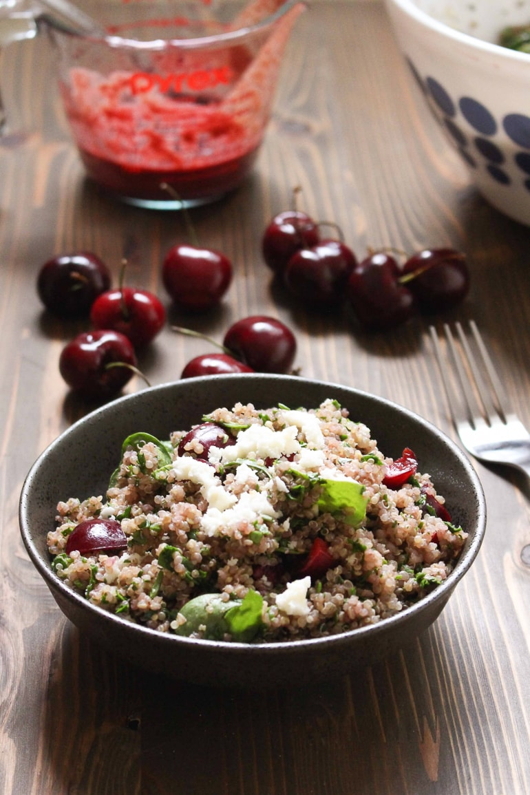 bowl with quinoa salad and cherries on table