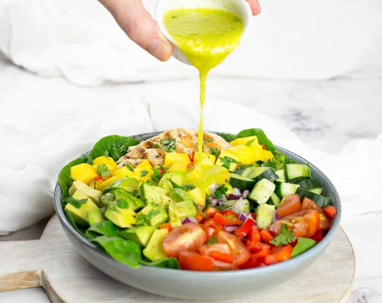 mango salad in bowl with dressing poured over