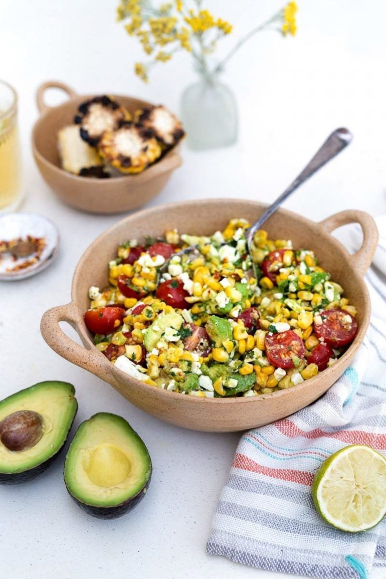 corn tomato avocado salad in neutral colored bowl with avocado and lime next to it