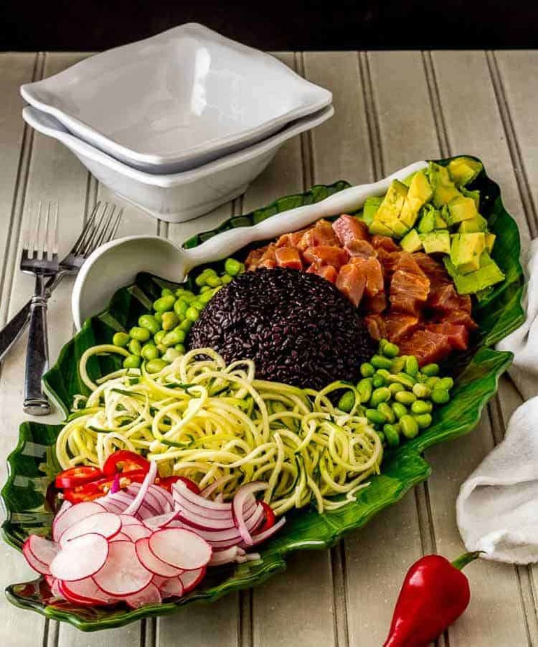 green bowl filled with tuna poke noodles and vegetables