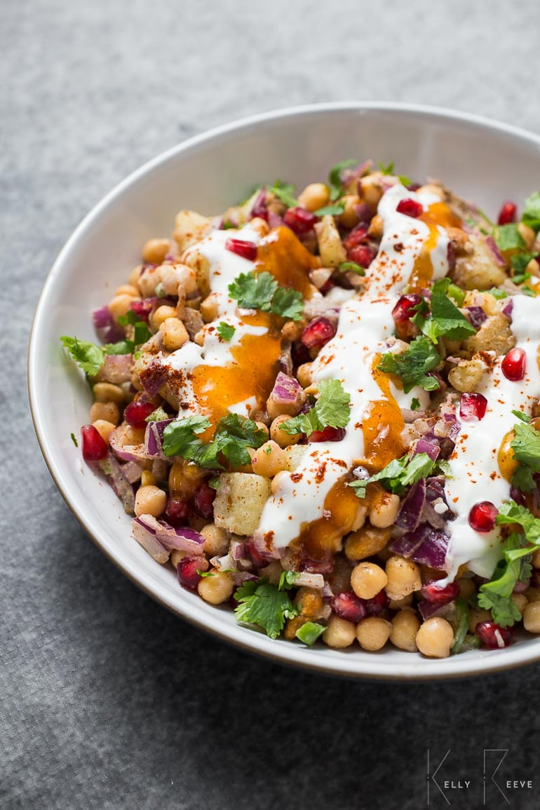 Chickpea salad with pomegranates, greens and dressing in white bowl