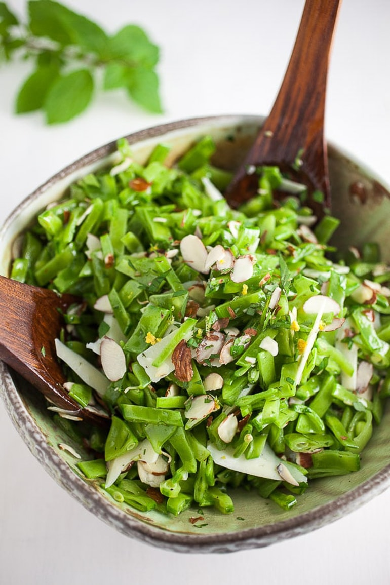 Green pea salad in bowl with wooden spoons