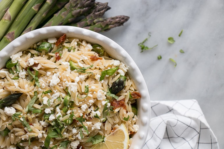 Orzo Pasta with asparagus and lime in white bowl with whole green asparagus next to it