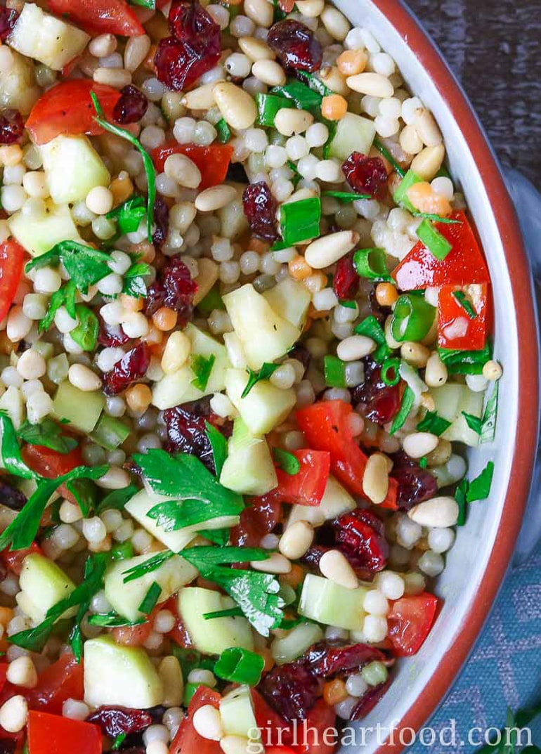 Couscous Salad with cut up vegetables in bowl close up
