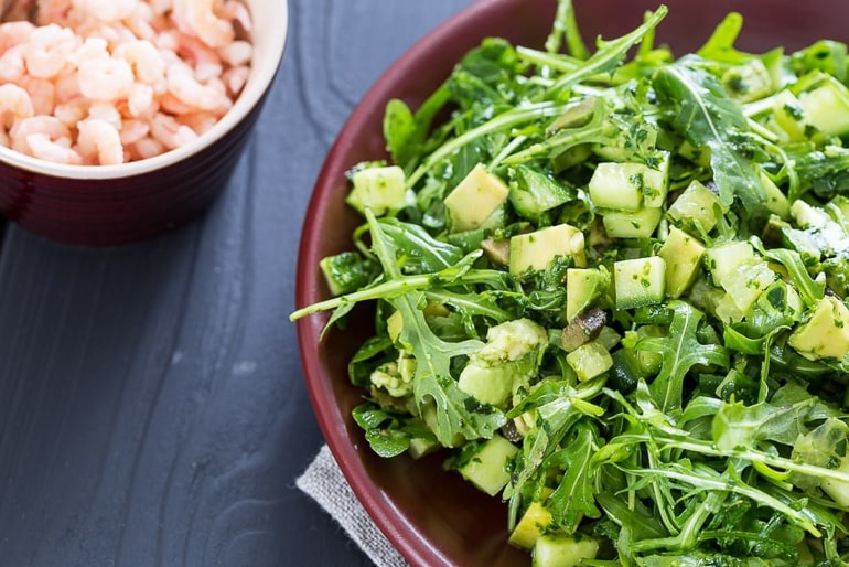 green salad in bowl with prawns on table