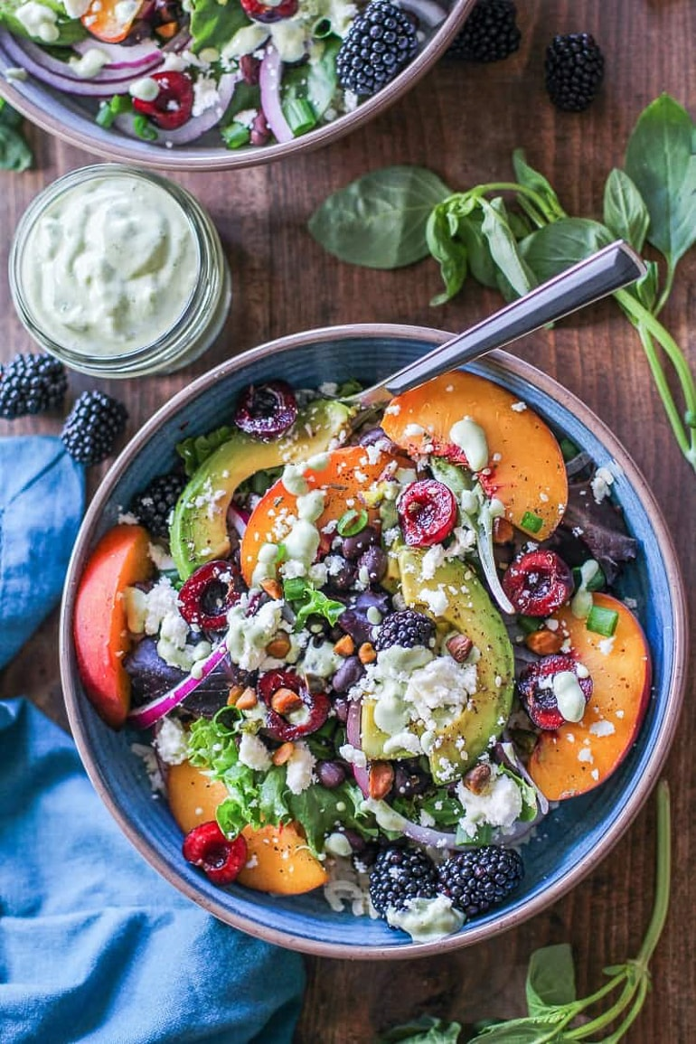 Salad with fruit, avocado and cheese in blue bowl on wooden table