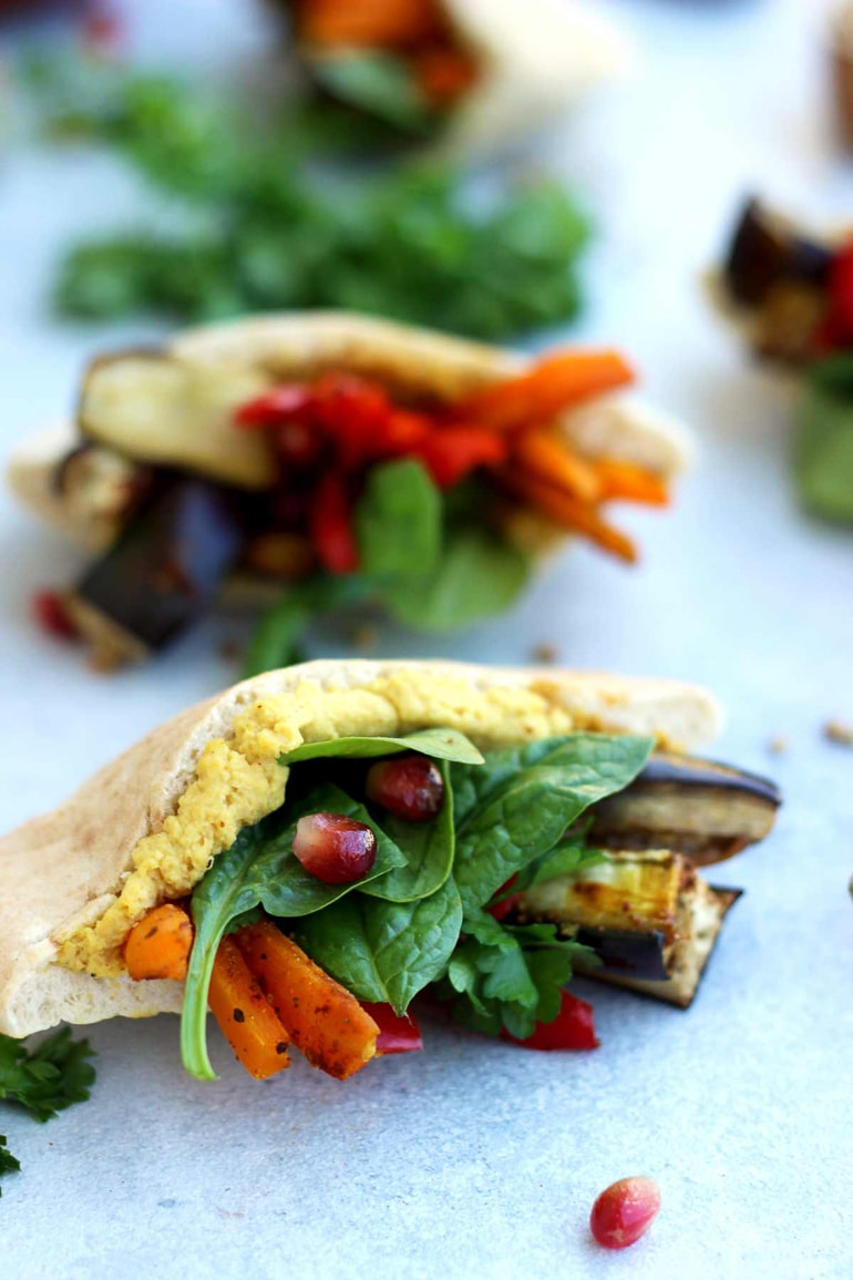 Cut up pita stuffed with hummus, spinach and grilled vegetables