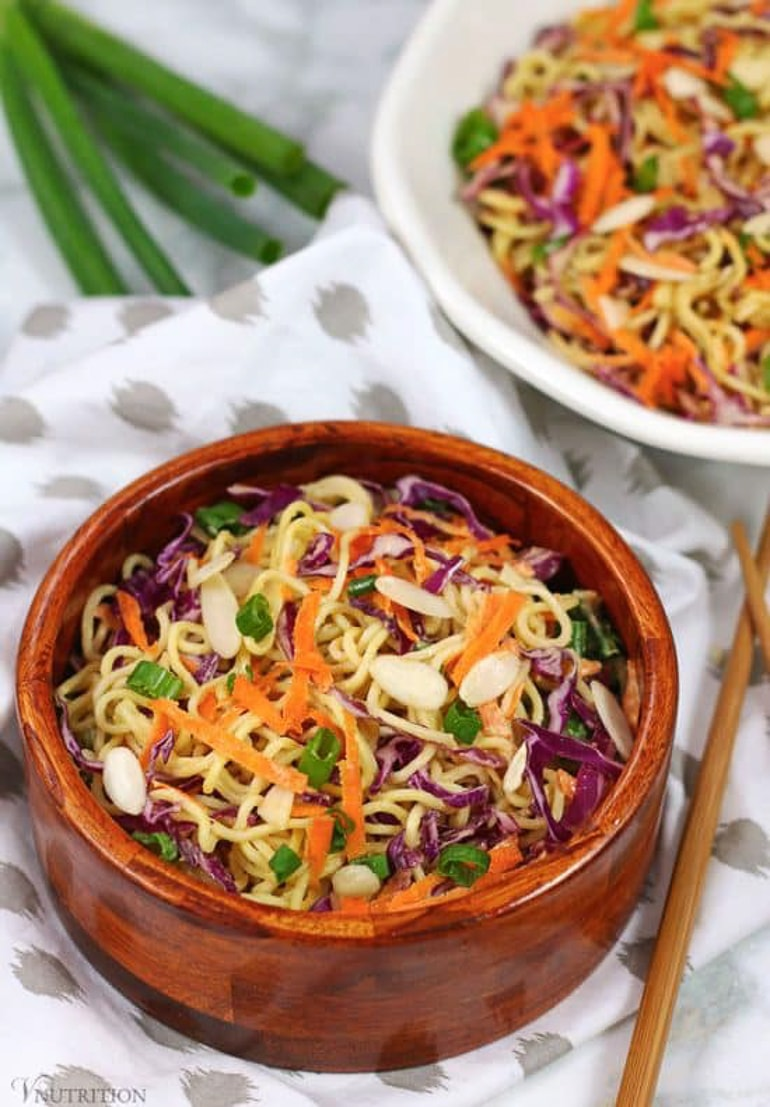 Ramen salad with shredded carrot and other vegetables in wooden bowl