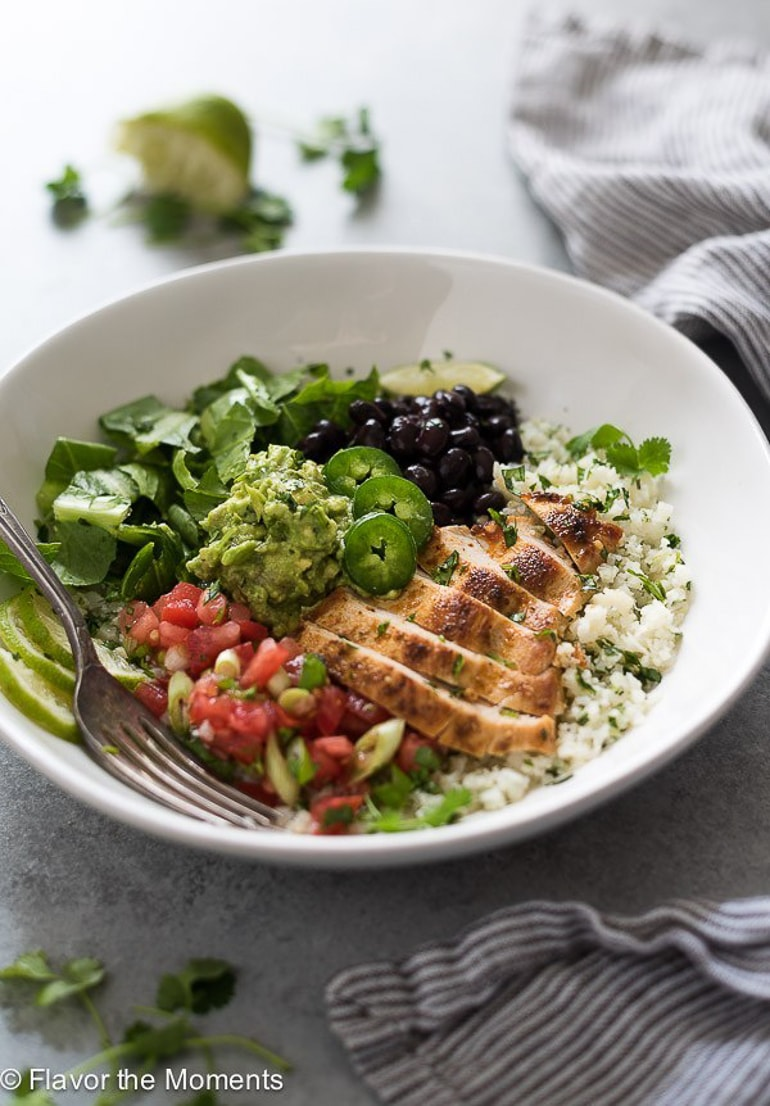 burrito bowl with chicken and avocado in white bowl