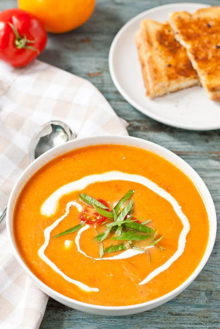Creamy Tomato Soup With Tomato Basil Garnish in white bowl