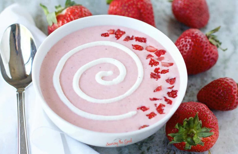Strawberry soup with white garnish in white bowl with spoon and whole strawberries next to it