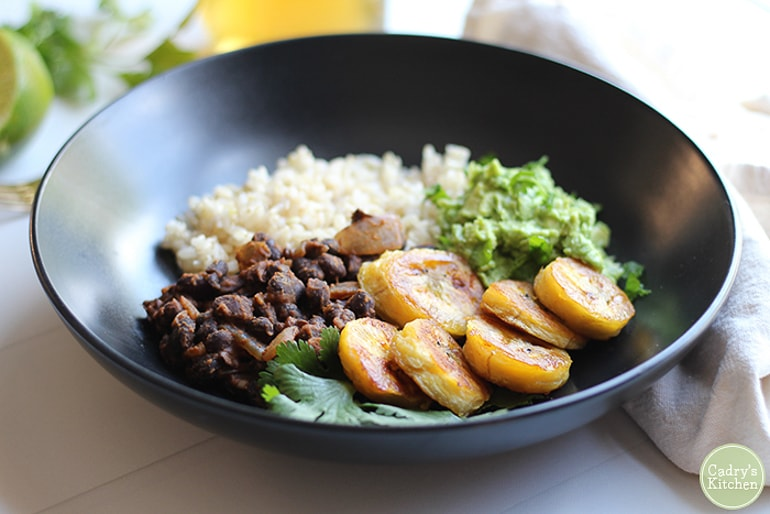 Blackbeans, rice, plantains and guacamole in black bowl