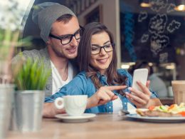 Couple sitting in a cafe with food in front of them looking at a smartphone apps for couples