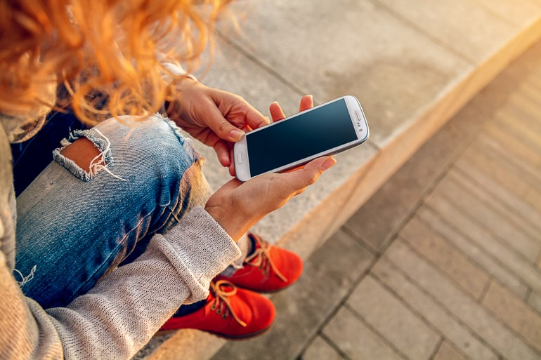 Woman with jeans and curly hair looking at a smartphone in her hand couples apps