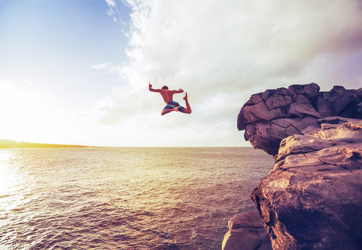 man jumping off cliff into water being a yes person