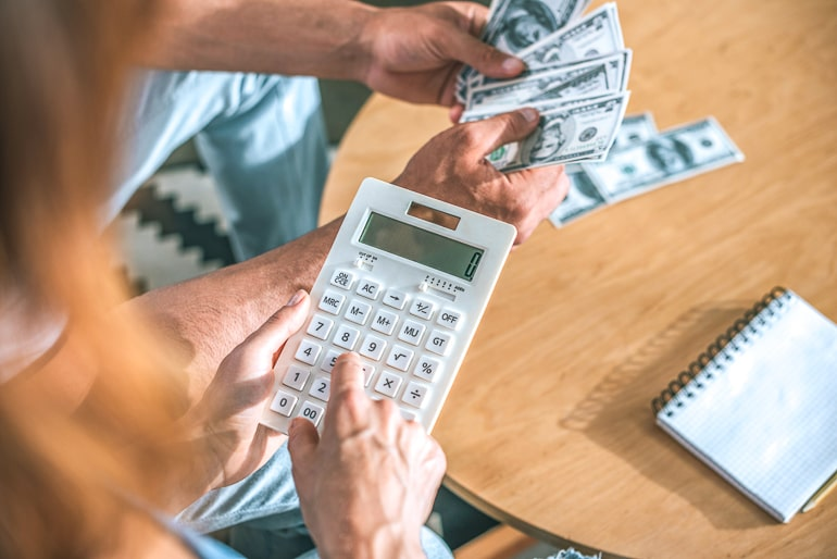 Woman holding white calculator with man in background holding money bills