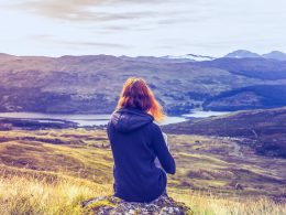woman sitting in rock with valley below best free meditation apps