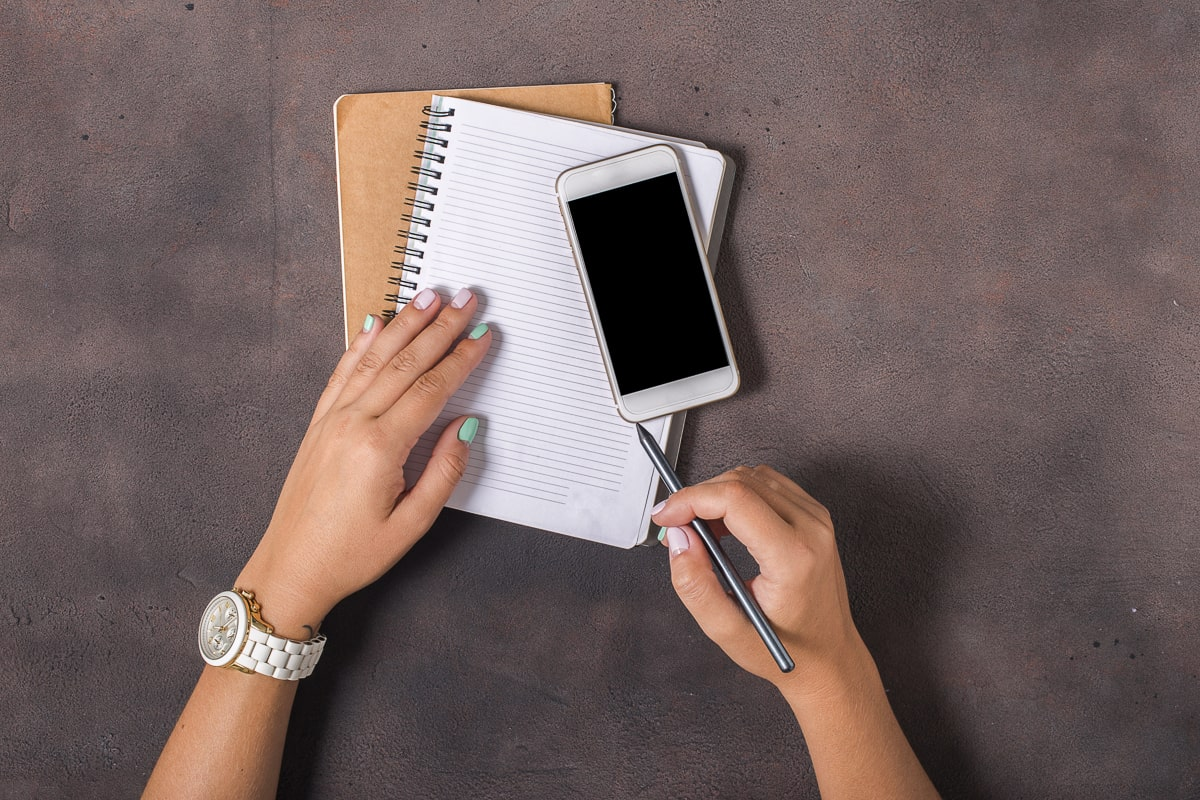 hands writing in notebook with phone on top best to do list apps