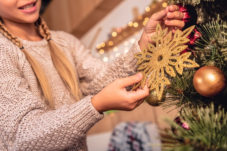 Female with braided hair and knitted sweater hangling star ornament on christmas tree