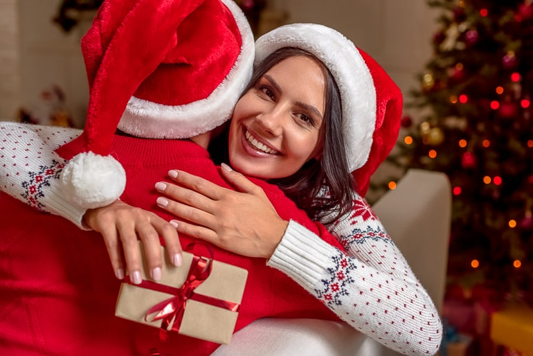 woman and man with christmas sweaters and christmas hats hugging with one person holding gift
