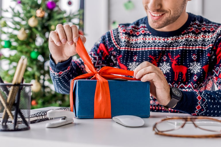 Man in christmas sweater unwrapping gift with blue paper and orange ribbon on desk