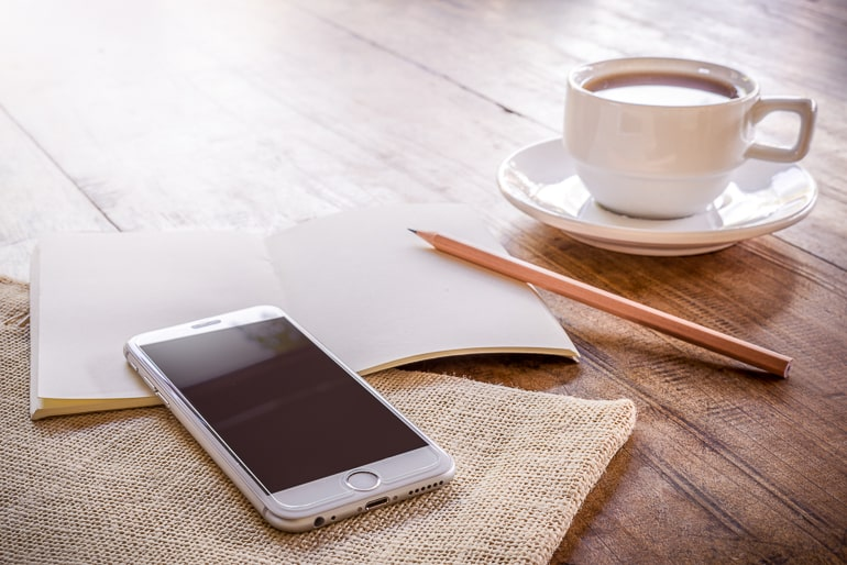 Phone notebook pencil and white mug on brown wood background