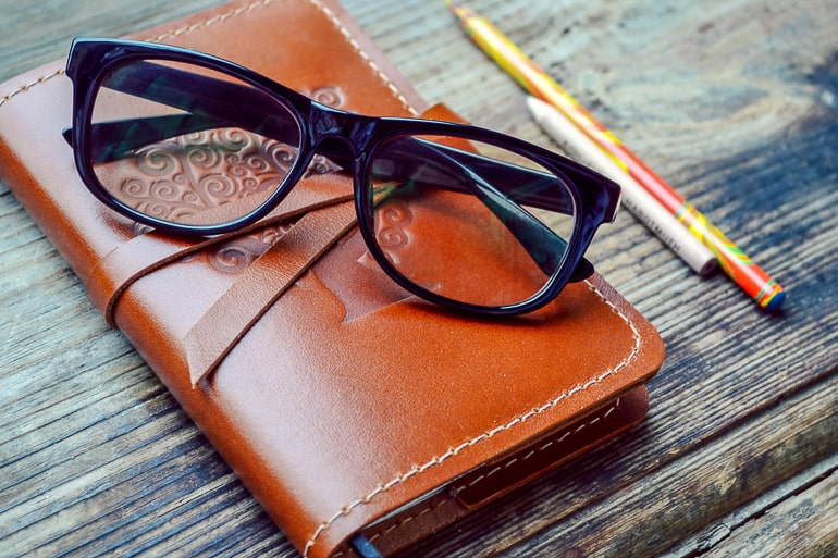 leather notebook with pencils and black glasses on dark wood