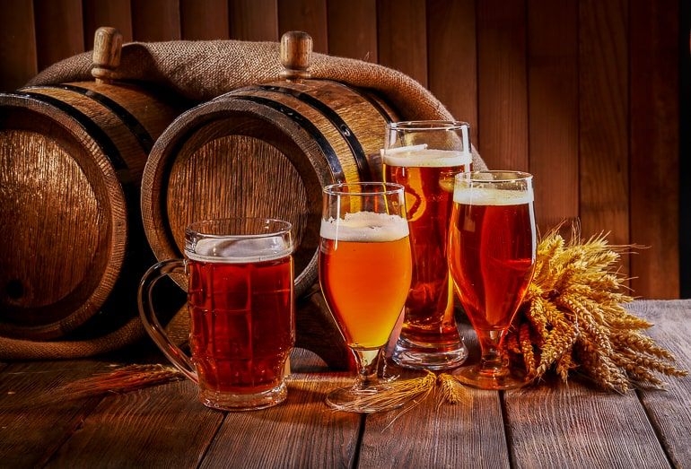 Different beer glasses standing in front of beer kegs on wooden table