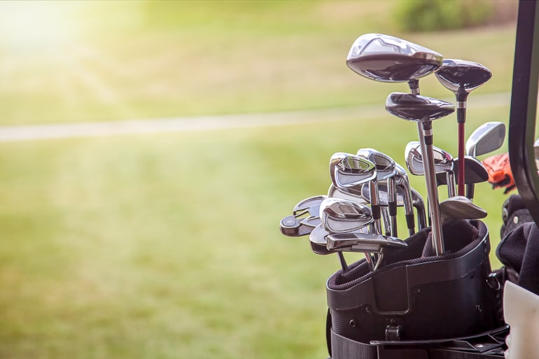 Bag full on golf clubs with green grass in background