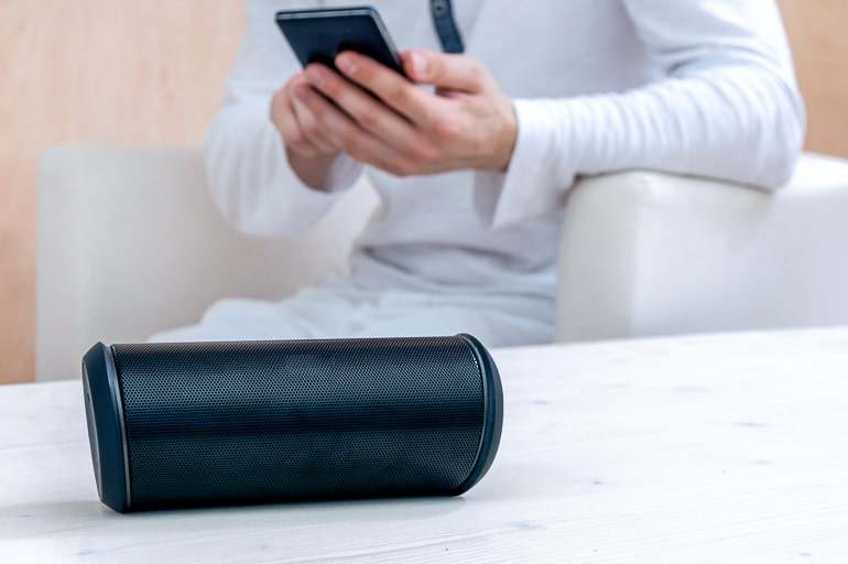 Portable speakers standing on white table with person in background holding a dark phone gifts for dads