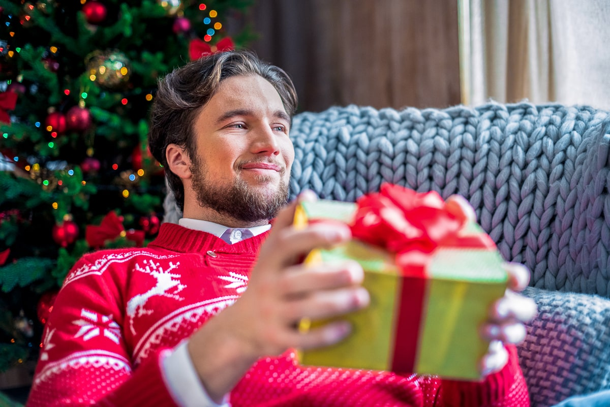 Man in red christmas sweater holding gift in his hand christmas gifts for dads