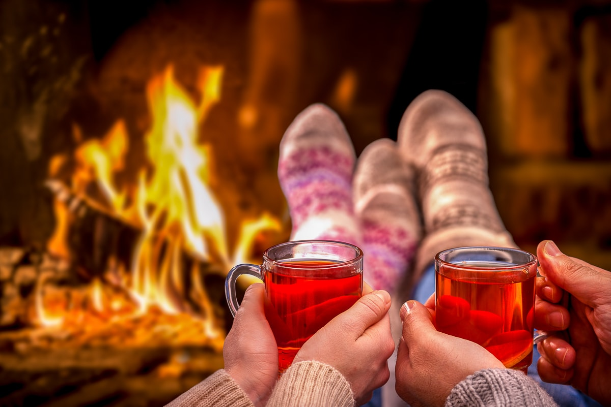 festive sock feet with warm red drinks in front of fire christmas onesies for adults