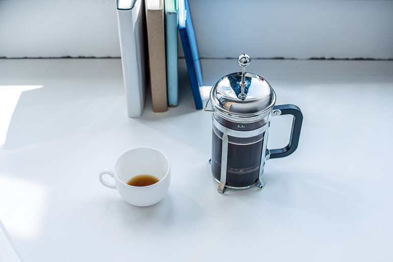 silver french press with coffee mug on white counter coffee brewing methods