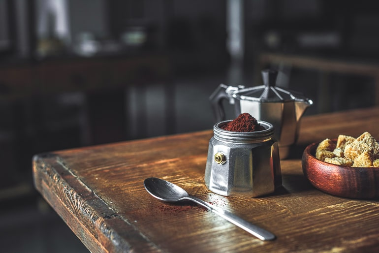 silver moka pot with coffee grounds and spoon beside