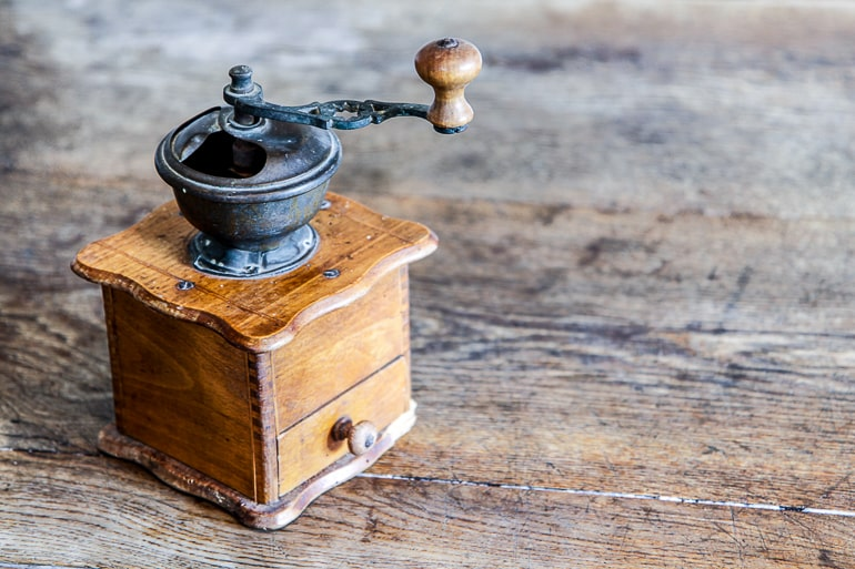 Vintage coffee grinder on wood background