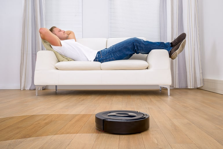 Man laying on white couch with robot vacuum cleaner in foreground cool gifts
